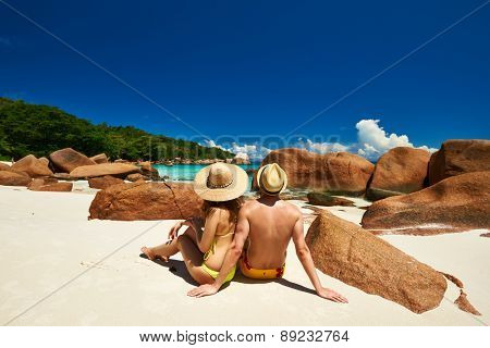 Couple sitting on a tropical beach at Seychelles
