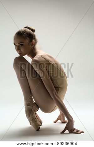 Graceful ballerina in a solid swimsuit sitting