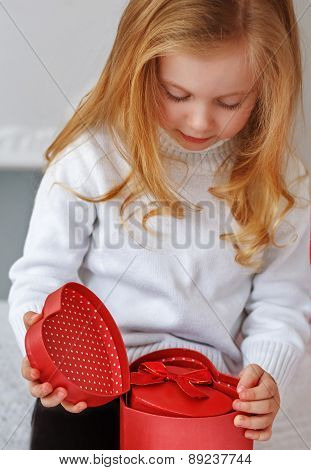 Little Girl Holding Present In Hands