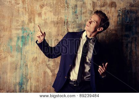 Expressive young man in elegant suit posing by a grunge wall.
