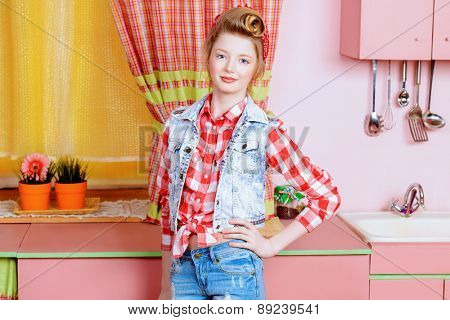 Pretty girl teenager wearing clothes and hair in pin-up style posing on a pink kitchen. Beauty, youth fashion. Pin-up style.