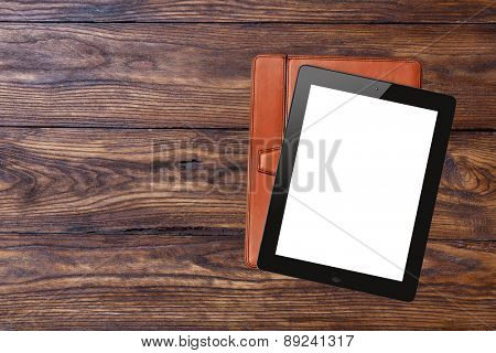 tablet pc with blank screen and brown case on wooden background, top view