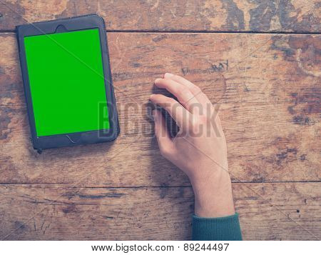 Hand And Tablet Computer On Wooden Table