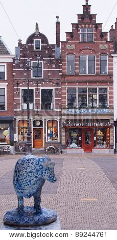 Delft pottery cow looking towards a Royal Delftware pottery