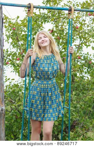 Blonde Student Girl Feminine Silk Sundress Is Standing On Handmade Swing