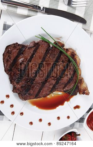 fresh rich juicy grilled beef meat steak fillet with marks on white plate over wooden table decorated with sauces and cutlery new york style