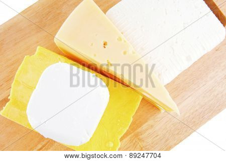goat cheeses and yellow on wooden board