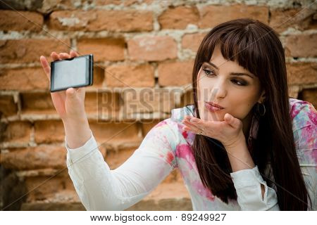 Woman blowing a kiss while taking selfie