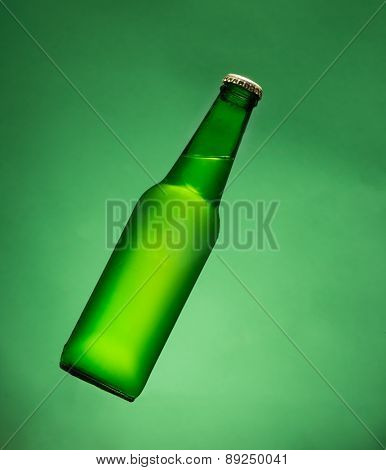 Green beer bottle in air.