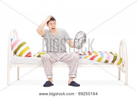 Shocked young man sitting on a bed in his pajamas and looking at the time isolated on white background