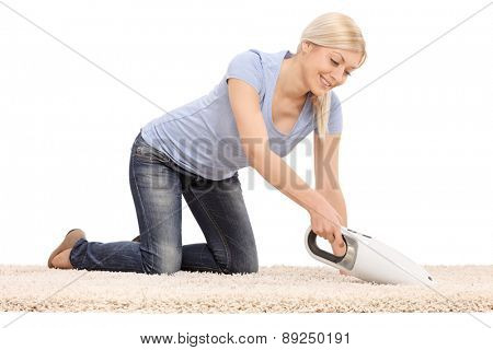 Young  blond woman cleaning a carpet with a handheld vacuum cleaner isolated on white background