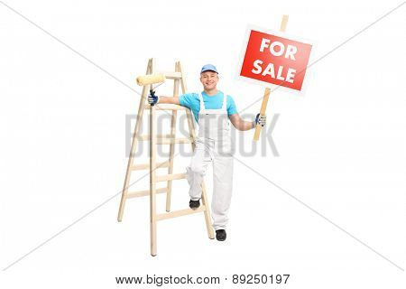 Full length portrait of a young male painter posing next to a wooden ladder and holding a paint roller in one hand and a for sale sign in the other isolated on white background