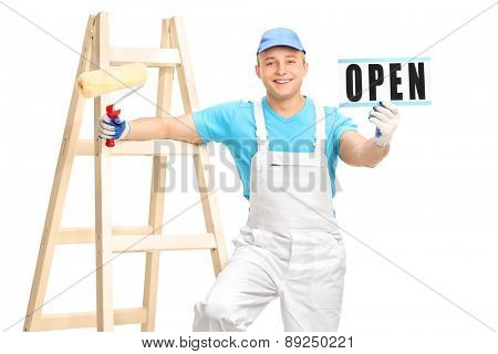 Young male house painter in a white jumpsuit and blue shirt holding a paint roller and an open sign isolated on white background