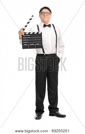 Full length portrait of a confident mature movie director holding a clapperboard and looking at the camera isolated on white background