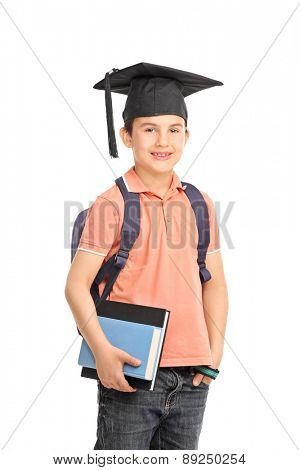 Schoolboy with a graduation hat carrying a backpack and holding a couple of books isolated on white background
