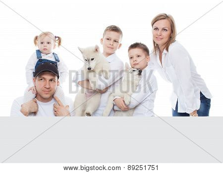 Beautiful family, mom, dad, kids, son, daughter, kids, puppies husky, with blank board, isolation