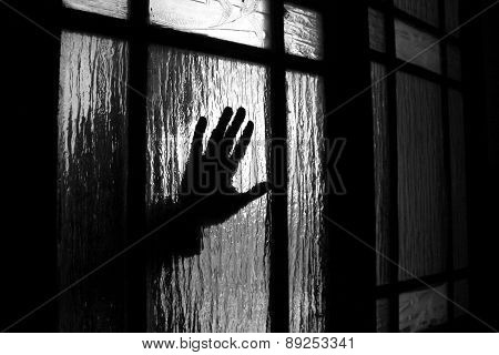 hand behind a glass door