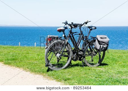 Two Bikes Parked On The Lawn At The Wide Blue Sea
