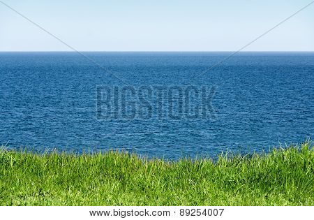 Green Grass In Front Of The Wide Blue Sea And Horizon To The Sky