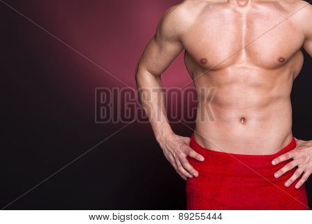 Fit man in red towel against dark background