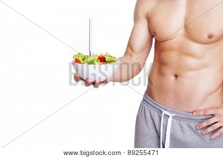 Muscular man holding a bowl of salad, isolated on white background