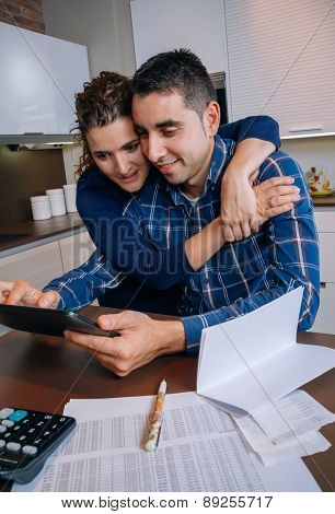 Cheerful couple using digital tablet at kitchen home