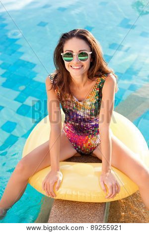 Woman With Perfect Tanned Body Lying On Yellow Air Mattress