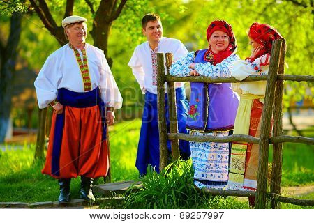 Happy Ukrainian Family In Traditional Costumes Talking Near The Wooden Fence
