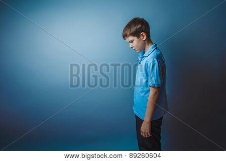 boy teenager European appearance in a blue shirt brown hair hung