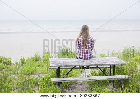 Rear view of young girl with long blond hair sitting on old beach picnic table facing ocean wearing plaid shirt