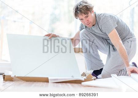 Man Unpacking Flat Pack Components