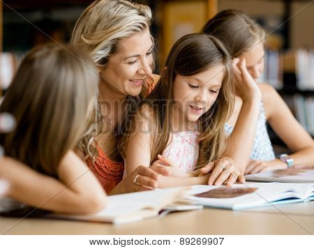 Little girls with their mother reading books in library