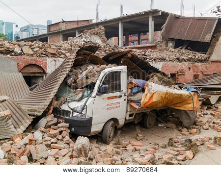 KATHMANDU, NEPAL - APRIL 26, 2015: Crashed van by a collapsed building after the 7.8 earthquake hit Nepal on 25 April 2015.