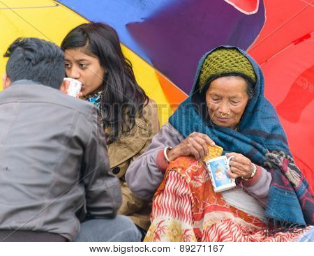 KATHMANDU, NEPAL - APRIL 26, 2015: People drinking tea on an open ground at Chuchepati after their first night outside after the 7.8 earthquake on 25 April 2015.