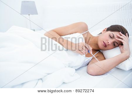 Sick woman looking at her thermometer at home in the bedroom