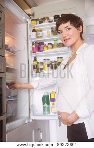 Pregnant woman opening the fridge at home in the kitchen