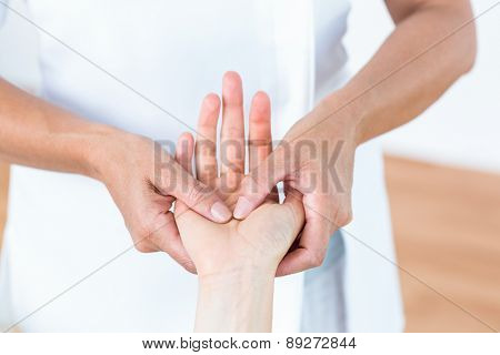 Physiotherapist massaging her patients hand in medical office