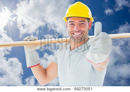 Worker with plank of wood against bright blue sky with clouds