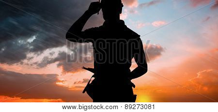 Portrait of smiling manual worker holding clipboard against orange and blue sky with clouds