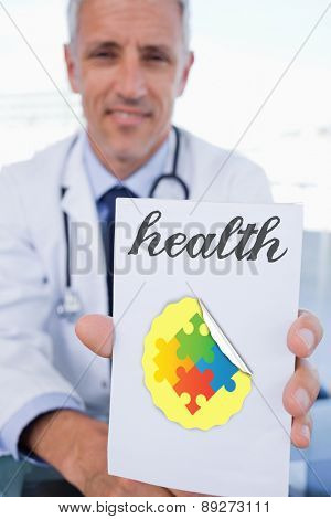 The word health and portrait of a male doctor showing a blank prescription sheet against autism awareness jigsaw