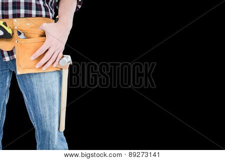 Handyman wearing tool belt against black