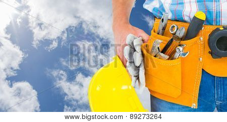 Manual worker wearing tool belt while holding gloves and helmet against bright blue sky with clouds