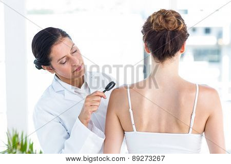 Doctor examining patient with magnifying glass in medical office