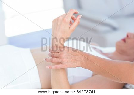 Physiotherapist examining her patients wrist in medical office