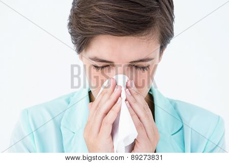 Casual brunette blowing her nose on white background