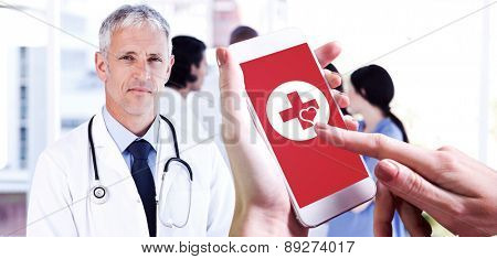 Hand holding smartphone against mature doctor pointing at something on his clipboard