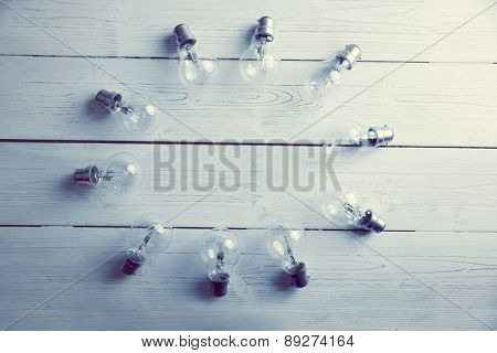 Light bulbs forming frame on wooden table