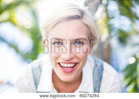 Pretty blonde woman smiling at the camera in the park