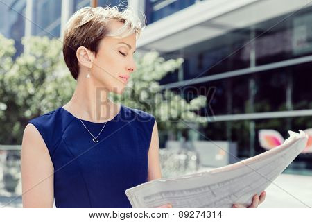 Businesswoman standing next to her office with newspaper