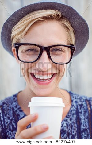 Pretty blonde woman holding goblet on wooden background